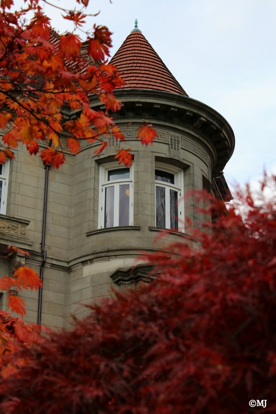 The Pittock Mansion through fall leaves.