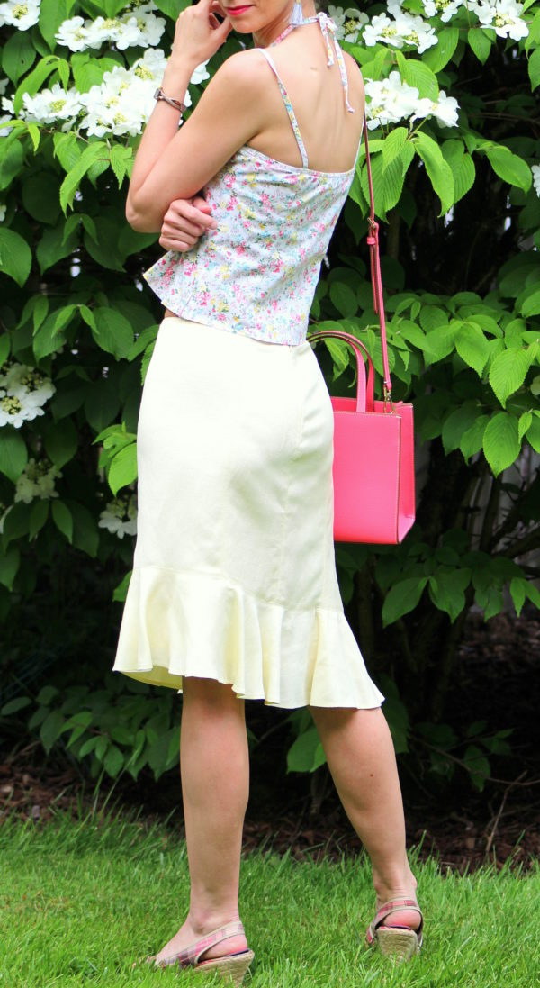 Floral tank top, yellow ruffled skirt, ivory sweater, flamingo pink handbag + plaid wedge heels