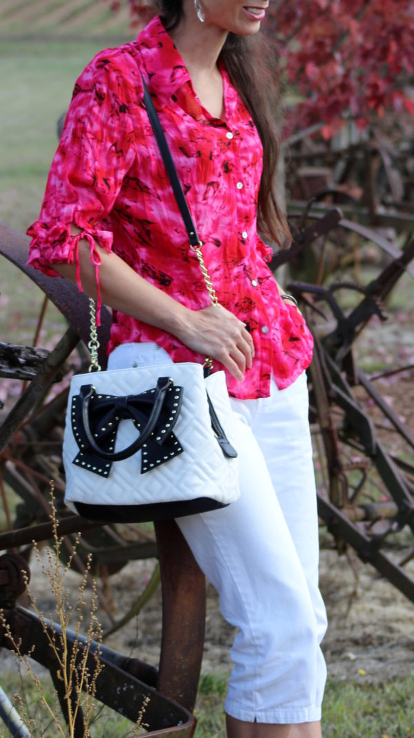 Pink and black ruffled 3/4 sleeve top, white capris +Betsey Johnson bow bag