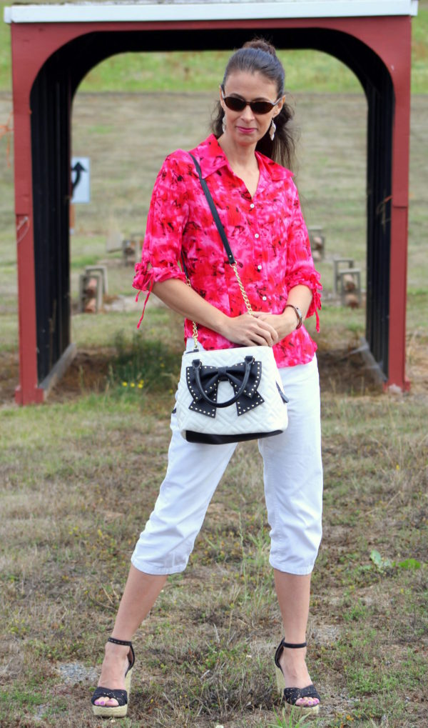Pink and black ruffled 3/4 sleeve top, white capris, black wedge heels, tortoise shell sunglasses + black and white Betsey Johnson purse