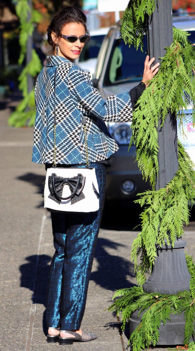 Tweed jacket, shiny blue pants, Betsey Johnson handbag, small tortoiseshell sunglasses, black ruffled top + metallic flats
