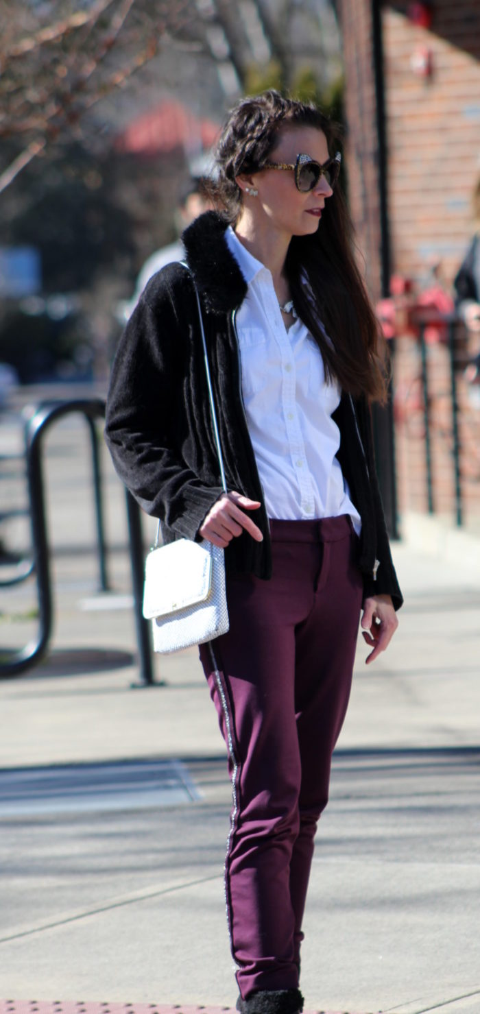 Burgundy pants, white button up shirt, black faux fur collar cardigan, black booties, white retro purse,and cat eye sunglasses